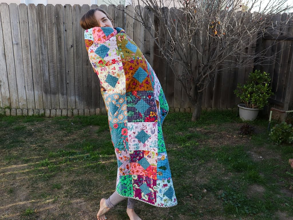 Miranda wrapped in her completed pandemic quilt.