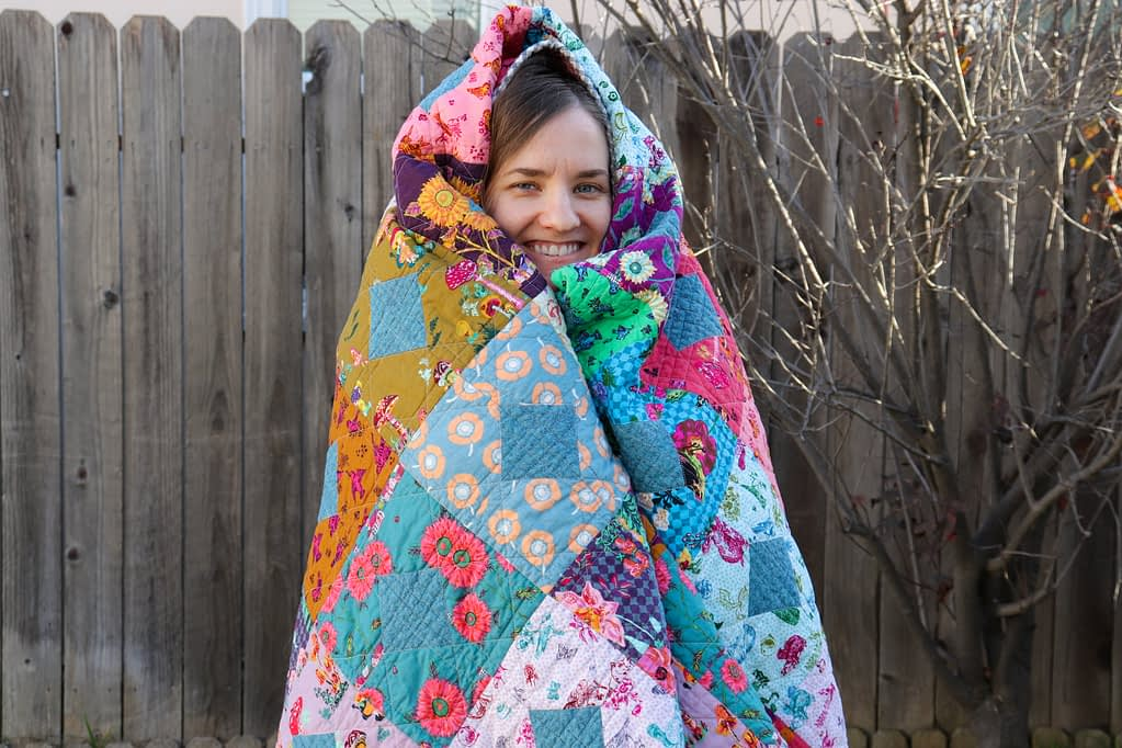 Miranda wrapped in her completed Diamond and Squares quilt.
